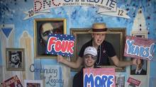 Stephen Kimel and his wife Greta Kimel attract costumers to take pictures at their photo booth which was set-up at a street festival for convention goers ahead of the Democratic National Convention in Charlotte, North Carolina on September 3, 2012. (ADREES LATIF/REUTERS)