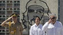 Uruguay's President Jose Mujica, right, stands in front of an image of revolutionary hero Ernesto Che Guevara during a wreath-laying ceremony at the Jose Marti monument in Havana, July 24, 2013. (ENRIQUE DE LA OSA/REUTERS)