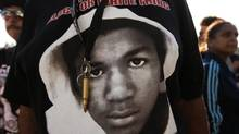 An image of Trayvon Martin and a bullet shell keychain hanging from a protester's lanyard are seen during a demonstration in reaction to the acquittal of neighborhood watch volunteer George Zimmerman on Monday, July 15, 2013, in Los Angeles.. (AP Photo/Jae C. Hong) (Jae C. Hong/AP)