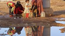 Syrian refugees collect water at Al Zaatri refugee camp in the Jordanian city of Mafraq, near the border with Syria September 26, 2013. REUTERS/Muhammad Hamed (JORDAN - Tags: POLITICS CONFLICT CIVIL UNREST SOCIETY) (MUHAMMAD HAMED/REUTERS)
