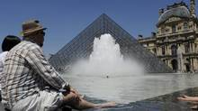 Tourists cool off in the fountains near the Pyramid entrance of the Louvre Museum on a hot summer day in Paris July 8, 2010. (GONZALO FUENTES/REUTERS)