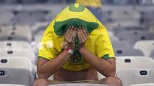 A Brazil fan covers his face after the World Cup semifinal soccer match between Brazil and Germany at the Mineirao Stadium in Belo Horizonte, Brazil, Tuesday, July 8, 2014. Germany beat Brazil 7-1 and advanced to the final. (Frank Augstein/AP Photo)