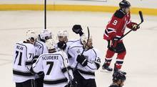 The Los Angeles Kings celebrate a goal by Colin Fraser (24) as New Jersey Devils' Zach Parise and Dainius Zubrus (bottom) skate away during the first period in Game 1 of their Stanley Cup final in Newark, New Jersey, May 30, 2012. (Shannon Stapleton/Reuters/Shannon Stapleton/Reuters)