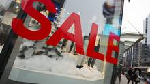 People walk by a sale sign in the window with Christmas decorations at a shopping mall in Toronto on Dec. 7, 2012. The federal Throne speech has set its sights on Canadian consumers, pledging a series of changes to the way Canadians shop, spend and save. (MARK BLINCH/REUTERS)