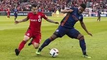 Toronto FC Sebastian Giovinco, left, battles for the ball with New York City FC Ethan White during the first half of MLS soccer action in Toronto on May 18, 2016. (Mark Blinch/THE CANADIAN PRESS)