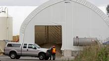 An RCMP officer and an unknown official talk in front of tent containing manure at a mushroom farm in Langley, B.C., on Sept. 6, 2008, after three people were overcome by an unknown substance and died and three were seriously injured. (Darryl Dyck/The Canadian Press/Darryl Dyck/The Canadian Press)
