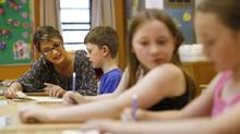 Grade 2 French teacher Natalie Ruel helps students in her class with math work at Mother Teresa elementary school in Calgary, Alberta on June 21, 2012. (TODD KOROL For The Globe and Mail)
