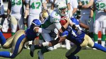 Saskatchewan Roughriders' Drew Willy (5) scrambles for yards against Winnipeg Blue Bombers' Jason Vega (98) and Henoc Muamba (10) during the second half of their CFL game in Winnipeg Sunday, September 9, 2012. (John Woods/THE CANADIAN PRESS)