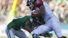 Saskatchewan Roughriders cornerback Terrell Maze stops Calgary Stampeders running back Jon Cornish during the first half CFL action in Regina, Sask., Sunday, September 23, 2012. (Liam Richards/THE CANADIAN PRESS)