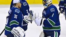 Vancouver Canucks goalies Roberto Luongo, right, and Cory Schneider tap gloves following the third period of their NHL hockey game against the Anaheim Ducks in Vancouver on Sunday. (ANDY CLARK/REUTERS)