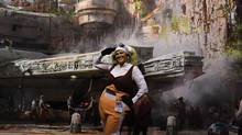 A woman poses for photos in front of a Star Wars backdrop during the D23 expo convention in Anaheim, Calif., on July 15, 2017. (MARK RALSTON/AFP/Getty Images)