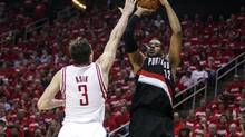 Portland Trail Blazers forward LaMarcus Aldridge shoots during the second quarter as Houston Rockets centre Omer Asik defends in Game 2 during the first round of the 2014 NBA Playoffs at Toyota Center. (Troy Taormina/USA Today Sports)