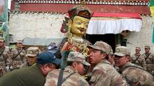 Soldiers of People's Liberation Army (PLA) remove a religious statue from a damaged lamasery after a 7.9-magnitude earthquake hit Nepal on Saturday, in Nyalam county, Tibet Autonomous Region, China, April 28, 2015. (REUTERS/China Daily)