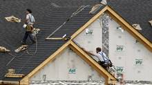 Roofers work on a new home construction site in Bridgeville, Pa. (Gene J. Puskar/AP)