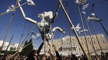 Protesters use a life-size puppet made of paper symbolizing a Greek during an anti-austerity rally in front of the parliament building in central Athens in this November 14, 2012 file photo. (JOHN KOLESIDIS/REUTERS)