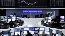 Traders work at their desks in front of the German share price index, DAX board, at the stock exchange in Frankfurt Nov. 8. (STAFF/REUTERS)