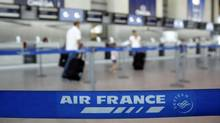 Passengers check-in at an Air France counter in Nice International airport July 26, 2012. A transatlantic flight made an emergency landing in St. John's Sept. 23, 2013. (ERIC GAILLARD/REUTERS)