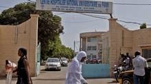 Women walk past the entrance to the University Hospital Fann, where a man is being treated for symptoms of the Ebola virus in Dakar, Senegal, Friday, Aug. 29, 2014. (Jane Hahn/AP)