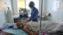 A nurse in Zhanaozen, Kazakhstan, attends to a man injured during Friday's riots. (Vladimir Tretyakov/Reuters)
