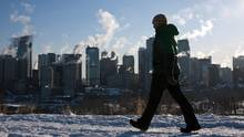 A man walks past a the Calgary, Alta., skyline as steam rises from downtown office towers Monday, Jan. 31, 2011. (Jeff McIntosh/THE CANADIAN PRESS)