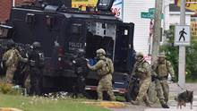 Emergency response officers enter a residence in Moncton, N.B. on June 5, 2014. (Andrew Vaughan/THE CANADIAN PRESS)
