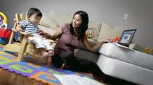 Stay-at-home mom, Samantha Li, sits with her 15-month old son, Emmett Li, while printing out some daily deal coupons at home in Toronto on Oct. 5, 2010. (Photo by Peter Power/The Globe and Mail)pmp (Peter Power/The Globe and Mail)