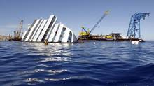 Capsized cruise liner Costa Concordia is surrounded by cranes, near the harbour of Giglio Porto, Aug. 28, 2012. (ALESSANDRO BIANCHI/REUTERS)