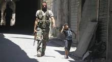 A member of the Free Syrian Army walks past a child in the old city of Aleppo, July 3, 2013. (MUZAFFAR SALMAN/REUTERS)