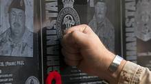 A soldier touches the plaque of a fallen comrade at the war memorial at Kandahar Air Field on Nov. 11, 2011. (RYAN REMIORZ/THE CANADIAN PRESS)