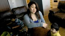 Jennifer Tanudjaja with her children at their home in Toronto's Jane-Finch area. (Peter Power/The Globe and Mail)