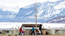 A family makes their way through the village of Pangnirtung, Nunavut. (Sean Kilpatrick/Sean Kilpatrick/The Canadian Press)