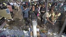 A woman reacts as she observes the candles and flowers left at a memorial event organized by the Muslim community to express their condemnation of the Westgate Mall attack, and to pay their respects to those who died and those who helped others escape, outside the Westgate Mall in Nairobi, Kenya Sunday, Sept. 29, 2013. Kenya's interior minister says that another arrest has been made Sunday in connection with the deadly Westgate mall attack, which left 67 people dead in a four-day siege, but refused to give any further details. (Ben Curtis/Associated press)