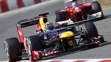 Red Bull Formula One driver Sebastian Vettel, left, drives ahead of Ferrari Formula One driver Fernando Alonso during a recent training session at the Circuit de Catalunya racetrack in Spain. (ALBERT GEA/REUTERS)
