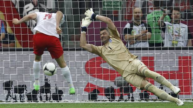 Poland's Robert Lewandowski (L) scores the first goal of the tournament past Greece's Kostas Chalkias during their Euro 2012 Group A match at the National Stadium in Warsaw, June 8, 2012. (Reuters)