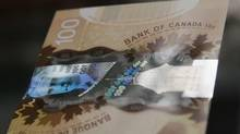 """Unlike the authentic polymer $100-bill, pictured, a hologram security feature on the counterfeit version is missing the """"100"""" on the transparent area. (Mark Blinch/Reuters)"""
