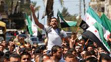 A protester shouts slogans as others wave Syrian opposition flags during a demonstration organized by Lebanese and Syrians living in Lebanon, against Syria's President Bashar al-Assad and to express solidarity with Syria's anti-government protesters, in Tripoli, northern Lebanon, April 13, 2012. (Omar Ibrahim/REUTERS/Omar Ibrahim/REUTERS)