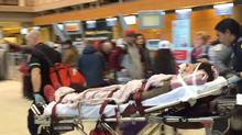 A passenger aboard an Air Canada flight is wheeled out of Calgary's airport after turbulence injured a number of passengers. (Courtesy of CBC)