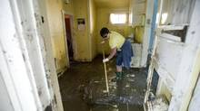 A volunteer removes post-flood sludge from inside a home in High River, Alta., July 7, 2013. (KEVIN VAN PAASSEN/THE GLOBE AND MAIL)