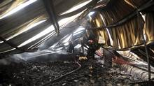 A Bangladeshi firefighter douses a fire at a garment factory in Gazipur outside Dhaka, Bangladesh, Wednesday, Oct. 9, 2013. The fire killed nearly a dozen people at the garment factory in Bangladesh. (AP)