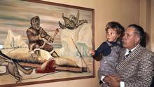 Stuart Hodgson holds a young Justin Trudeau in his arms to help him look closer at a painting of an Inuit hunter. (NWT Archives)
