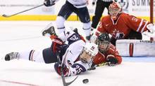 USA right wing Alex Carpenter (25) battles for the puck with Canada defenceman Meaghan Mikkelson (12) during the second period in an exhibition hockey game at Air Canada Centre. (Tom Szczerbowski/USA Today Sports)