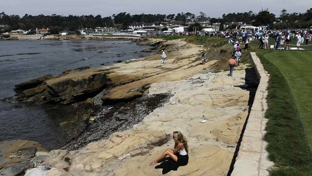 A guest sits on the shore along the 18th fairway during the Concours d'Elegance at the Pebble Beach Golf Links in Pebble Beach, California, August 17, 2014. (MICHAEL FIALA/REUTERS)