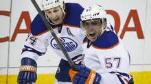 Edmonton Oilers' David Perron, right, celebrates his game-winning goal with teammate Ryan Smyth during third period NHL hockey action against the Calgary Flames in Calgary, Alta., Saturday, Nov. 16, 2013. The Edmonton Oilers beat the Calgary Flames 4-2. (JEFF MCINTOSH/THE CANADIAN PRESS)