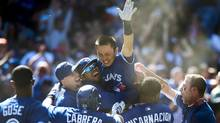 Toronto Blue Jays Munenori Kawasaki raises his arm to celebrate as he is hoisted by his team after hitting a game-winning walk off double against the Baltimore Orioles in AL action in Toronto on Sunday May 26, 2013. Jays won 6-5. (Frank Gunn/The Canadian Press)