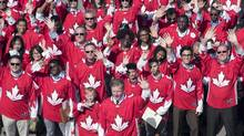 Former Ottawa Senators NHL player Daniel Alfredsson, front, joins new Canadian citizens, wearing Team Canada jerseys, at a citizenship ceremony for the World Cup of Hockey 2016 Legacy Project in Toronto on Sept. 20. (Mark Blinch/THE CANADIAN PRESS)