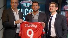 Toronto FC manager Ryan Nelsen (left) and GM Tim Bezbatchenko (right) flank new signing, Brazilian forward Gilberto. in Toronto on Friday December 13, 2013. (NEIL DAVIDSON/THE CANADIAN PRESS)