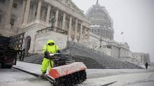 Snow is cleared outside the U.S. Capitol in Washington, Jan. 22, 2016. (ZACH GIBSON/NYT)
