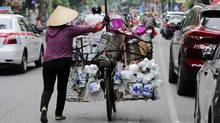 A vendor walks her merchandise on a bicycle along a street in Hanoi, Vietnam. (Luong Thai Linh/Bloomberg)