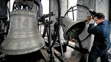 Bell repairman Daniel Desormiers examines the clapper on one of the bells at Notre Dame des Sept Douleurs church in Montreal on Dec. 14. (Peter McCabe for The Globe and Mail)