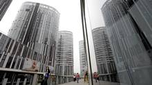 People walk along the Sanlitun SOHO residential and commercial complex in Beijing. (JASON LEE/JASON LEE/REUTERS)